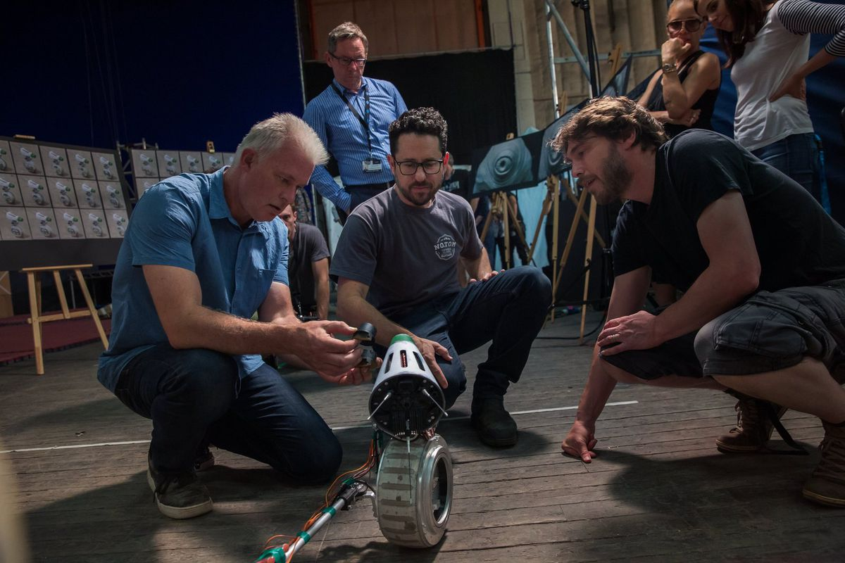 SFX supervisor Neal Scanlan, director J.J. Abrams, and an unidentified crew member squat in a circle around the droid D-O for an adjustment on the set of The Rise of Skywalker