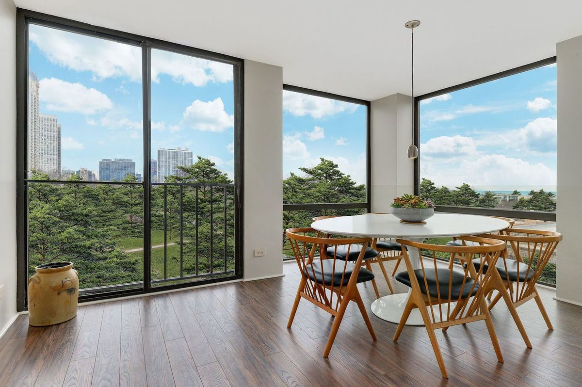 A dining area in the corner of the apartment surrounded by floor-to-ceiling windows. There is a circular Tulip table and six wooden chairs around it.