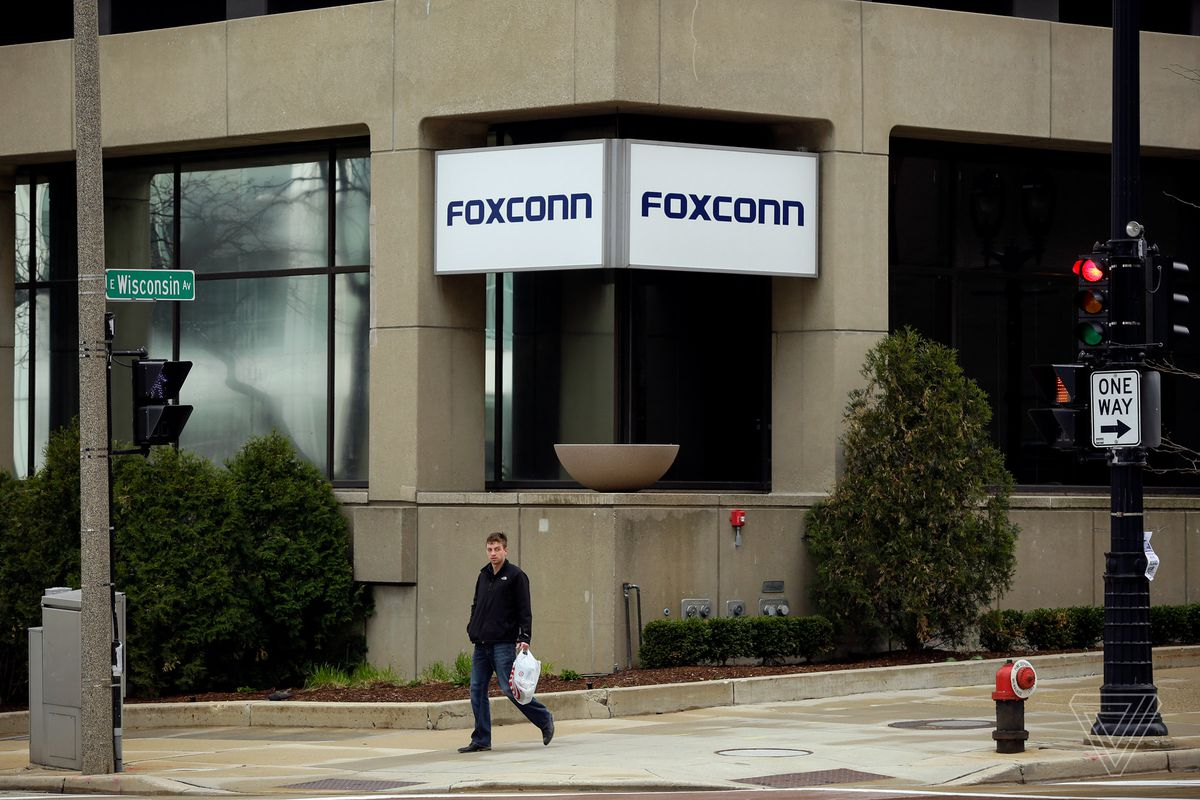 A man walks past an office building with the Foxconn name displayed outside on Wednesday, May 8 2019 in Milwaukee, Wisconsin. Foxconn is a electronics contract manufacturing company, which is constructing a plant in south eastern Wisconsin creating thousands of jobs.