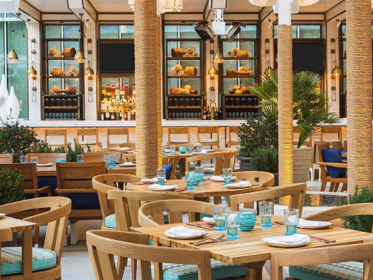 A patio with light wood chairs and tables set up with white plates and blue glasses with a bar in the background