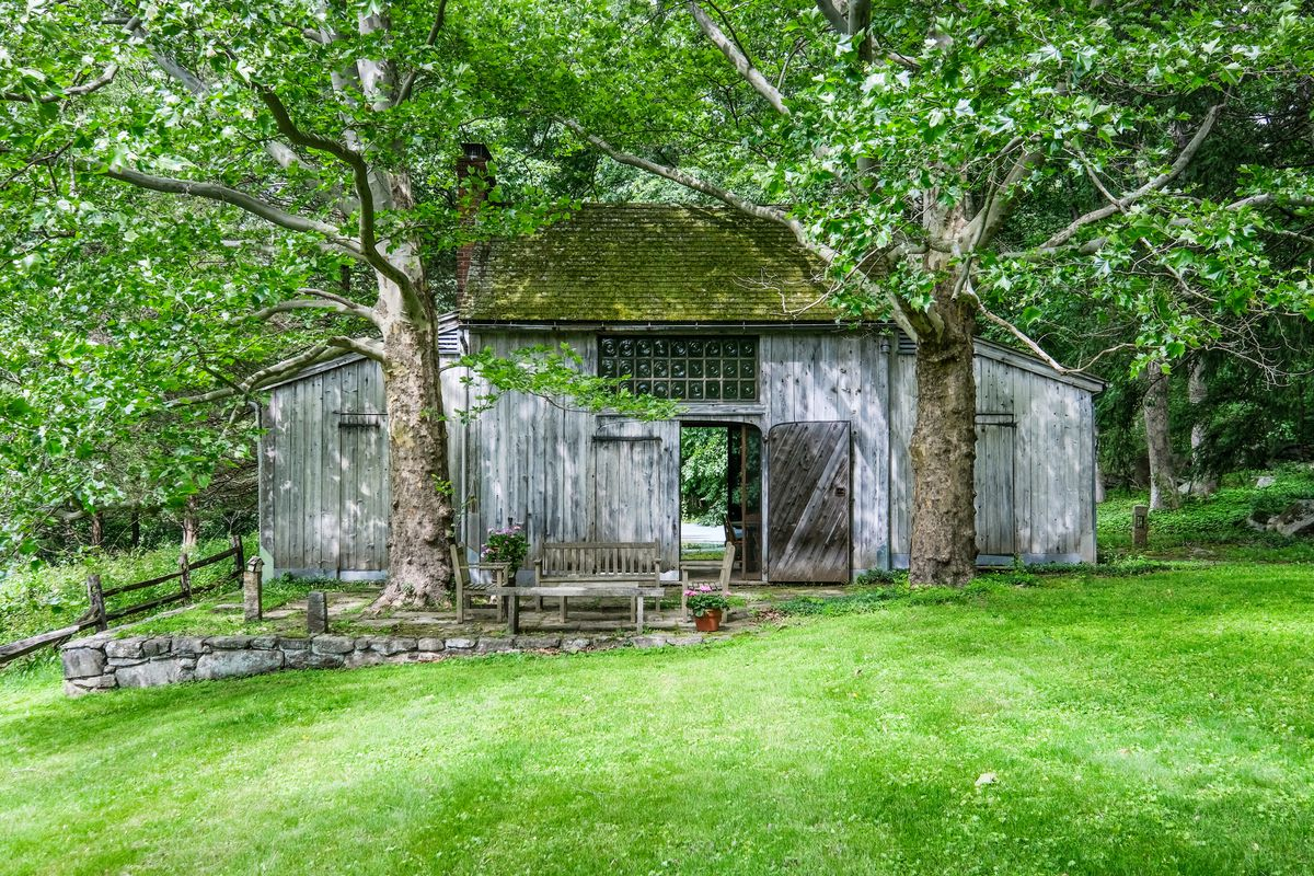 A old barn has trees in front of it, moss on the roof, and green grass surrounding it.