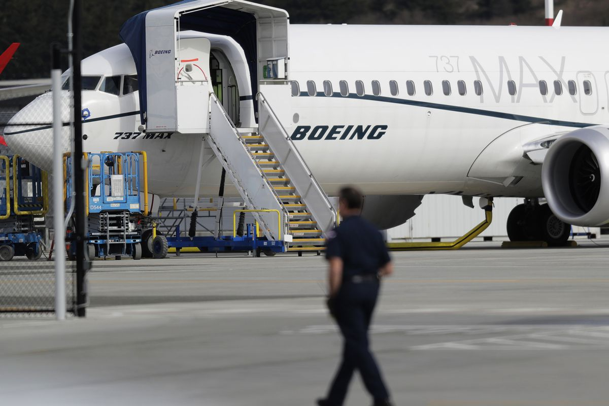 FILE - In this March 14, 2019, file photo, a worker walks next to a Boeing 737 MAX 8 airplane parked at Boeing Field in Seattle. U.S. aviation regulators said Monday, April 1, Boeing needs more time to finish changes in a flight-control system suspected o