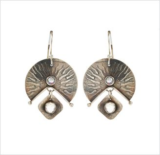 A pair of sunburst earrings and a ceramic bowl with a ruffled white outside and a blue glazed inside.