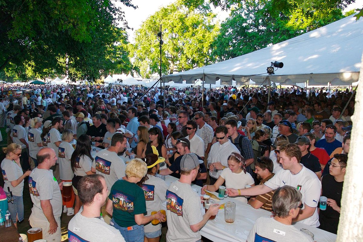 A mass of people stand at an outdoor bar while people serve beers
