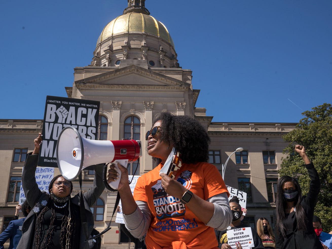 A woman stands in front of the Georgia Capitol holding a bullhorn.