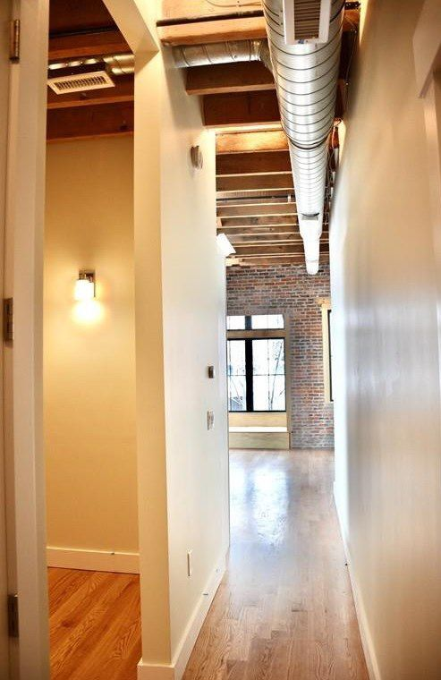 A long hallway toward an empty room with an air duct running above.
