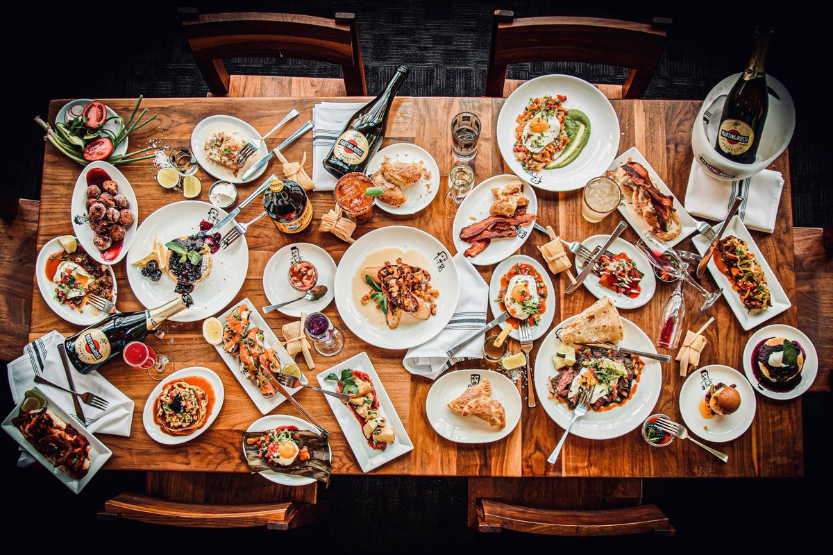 A rectangular wood table filled with brunch dishes on white plates.
