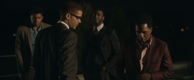 Four men stand together, in a pause in a moment of conversation.