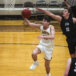 Davis guard Rex Sunderland gets past Layton's Carter Mayfield for a bucket during a boys basketball game at Davis High School in Kaysville on Friday, Jan. 22, 2021.