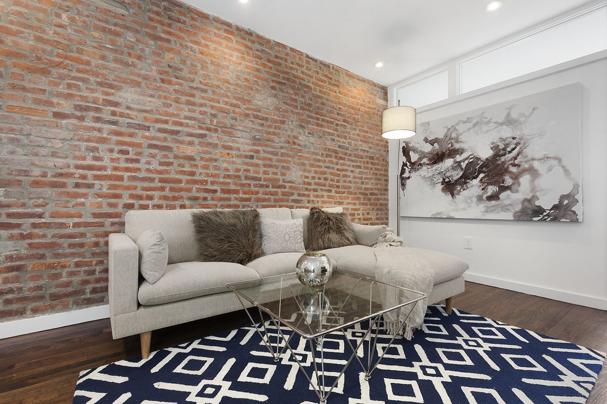 A living area with exposed brick, hardwood floors, a beige couch, and a glass coffee table.