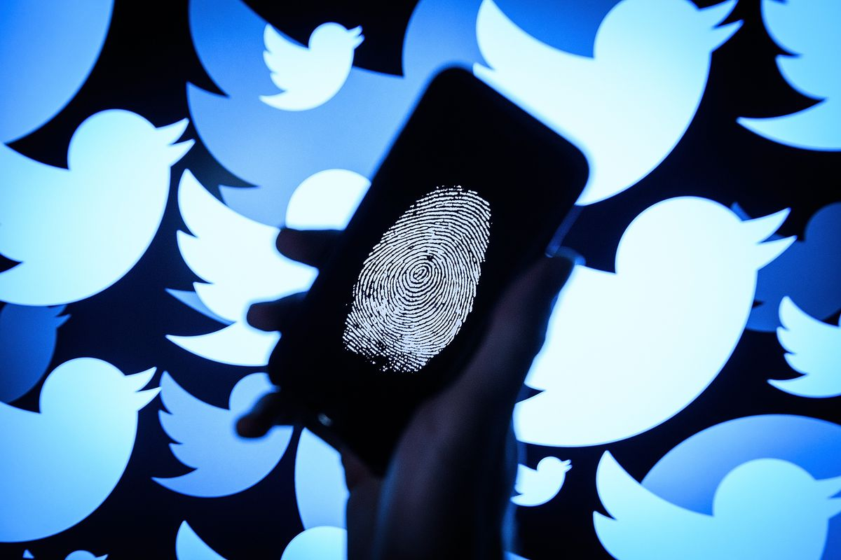 A fingerprint on a phone screen, with Twitter bird logos in the background