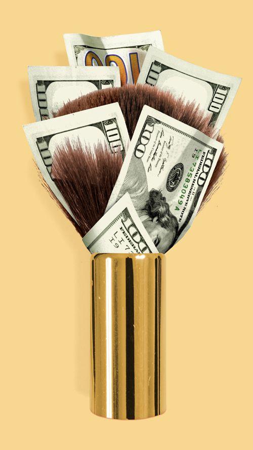 Makeup brush with dollar bills among the bristles