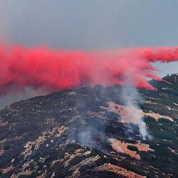 A heavy air tanker drops retardant on a fire burning near Weber Canyon on Tuesday, Sept. 5, 2017.