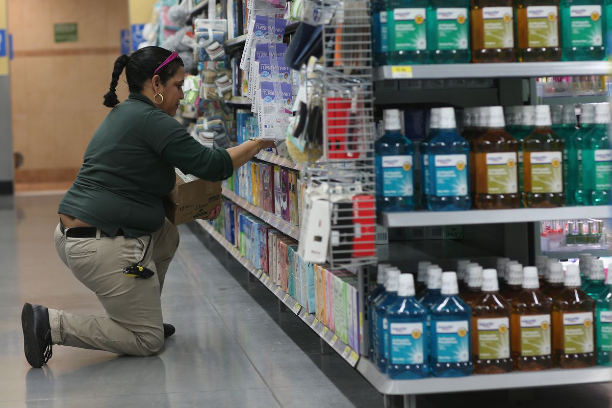A Walmart employee kneels on the floor while she stocks shelves in the pharmacy section.