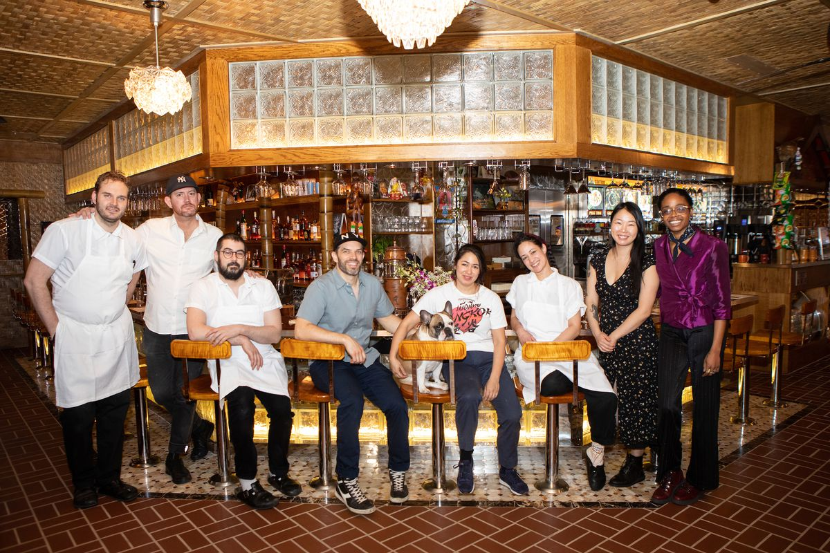 A group of people sit on stools and smile at the camera