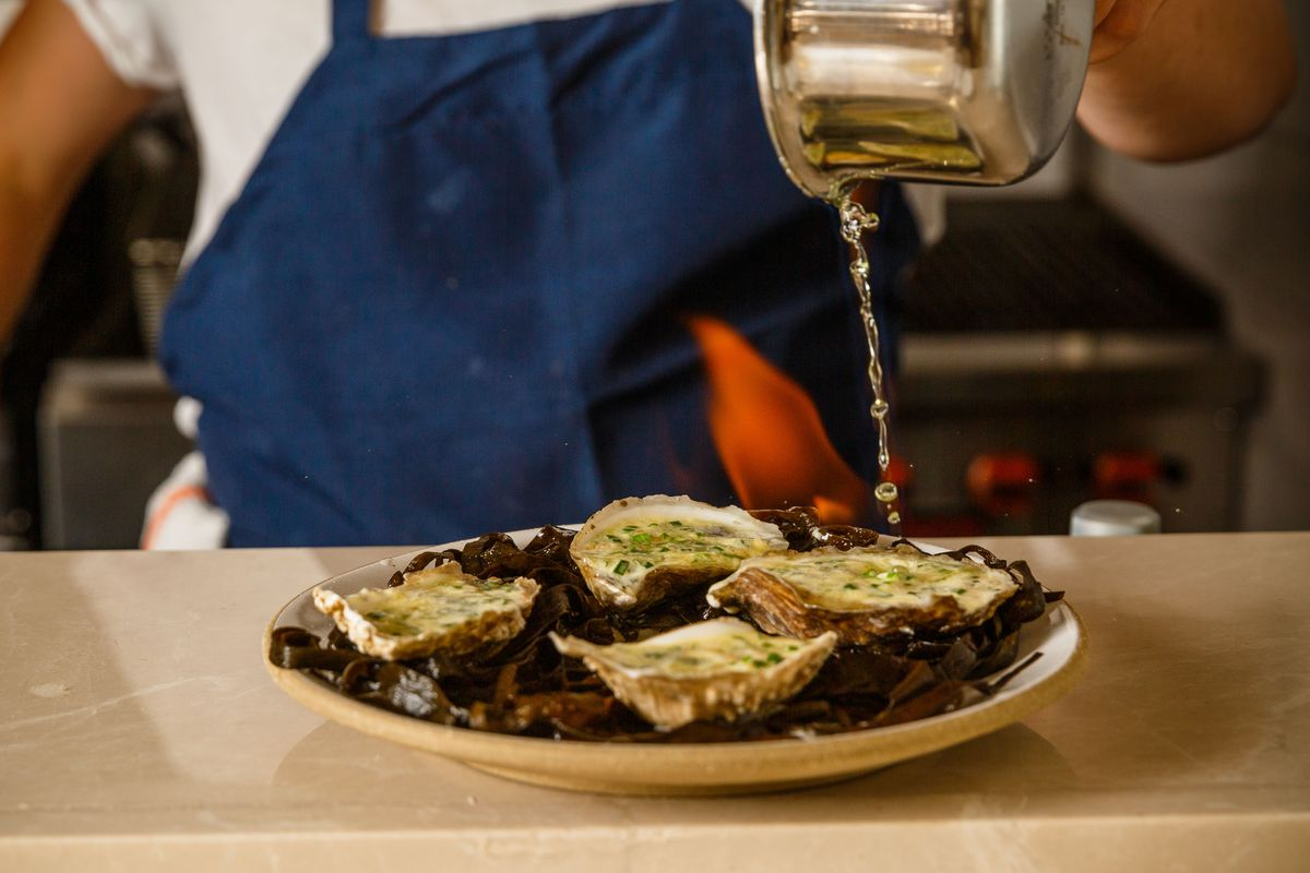 A plate of four oysters on strips of brown seaweed, set on a white plate, set on fire with a person pouring alcohol from a saucepan over top