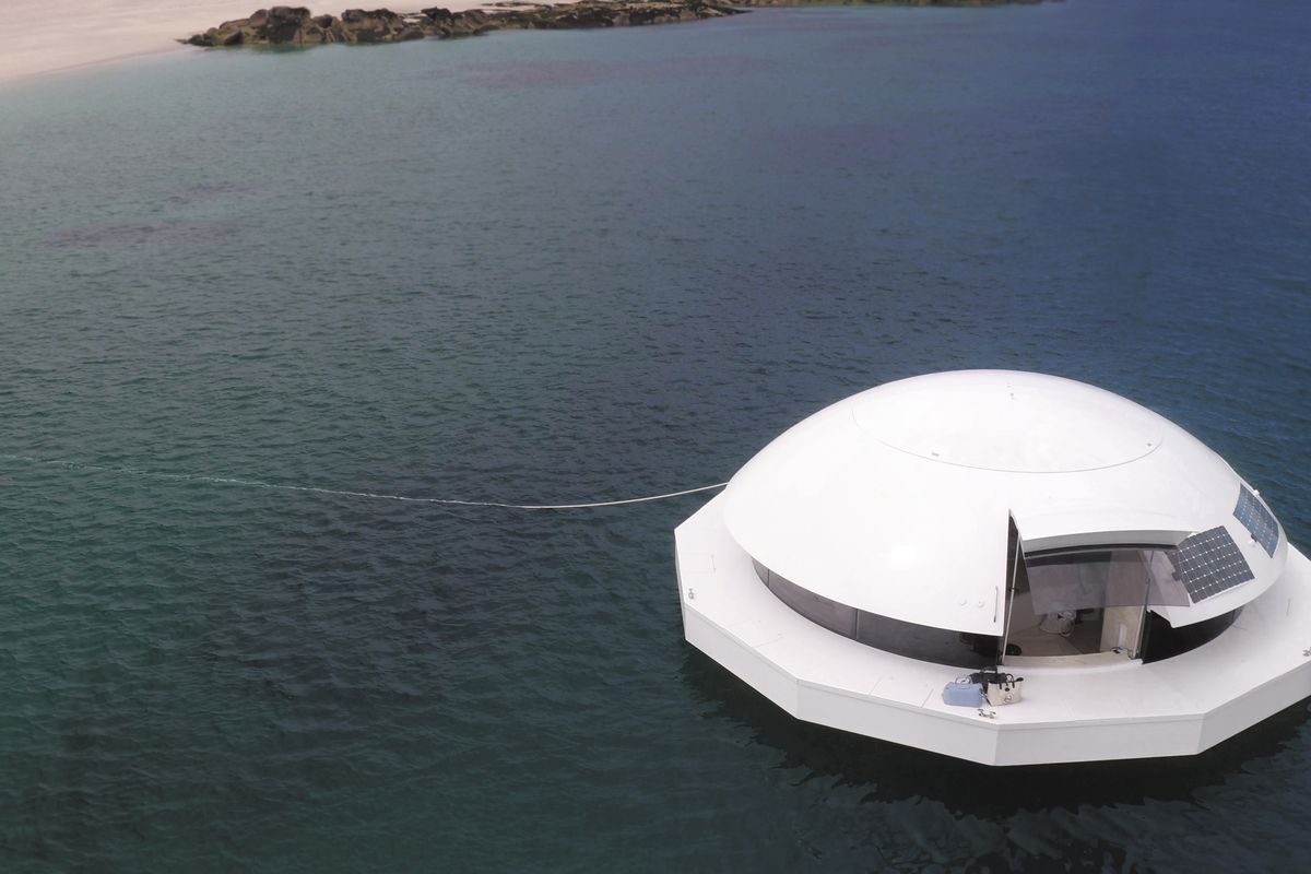 A white saucer-shaped floating dwelling on a boday of water. It has a domed shape top.