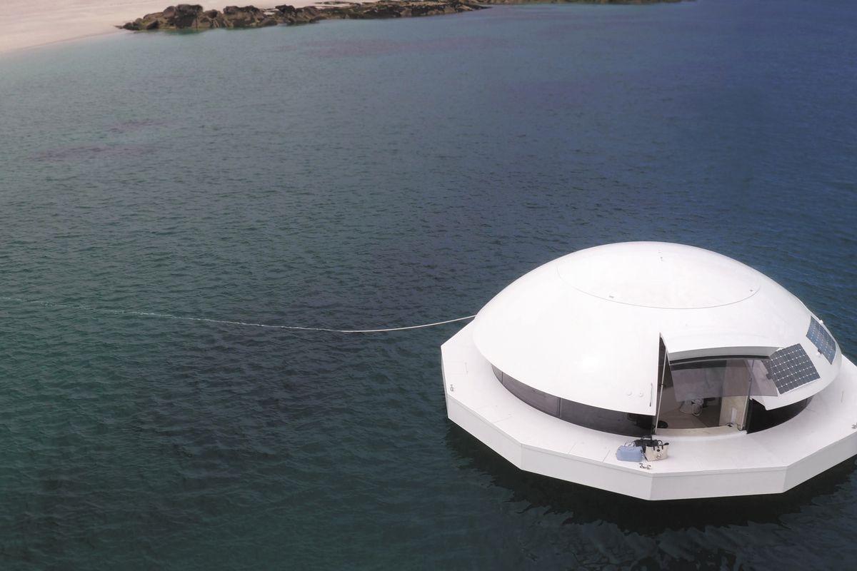 Белый блюдцевидный плавающий дом на бодай воды. Он имеет куполообразную форму сверху.