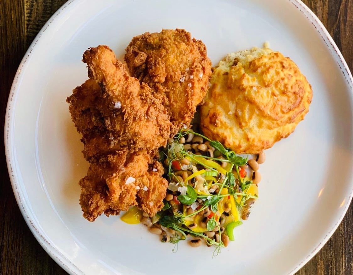 Plate of fried chicken with biscuit and vegetables