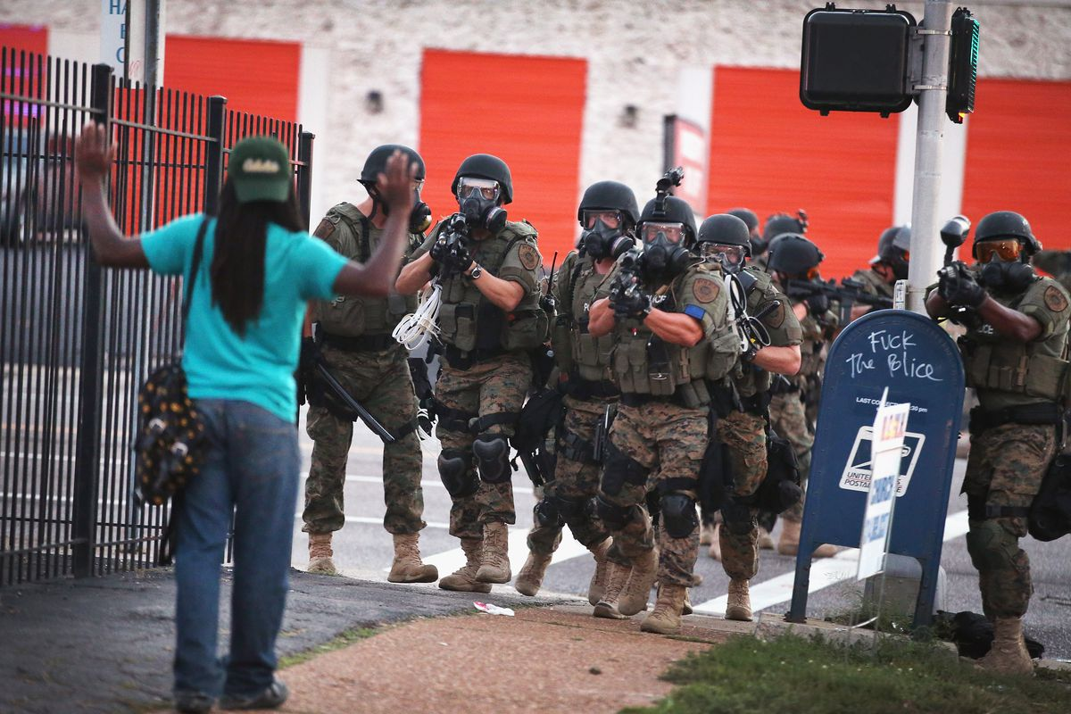 A man holds his hands up as he's confronted with police in Ferguson.