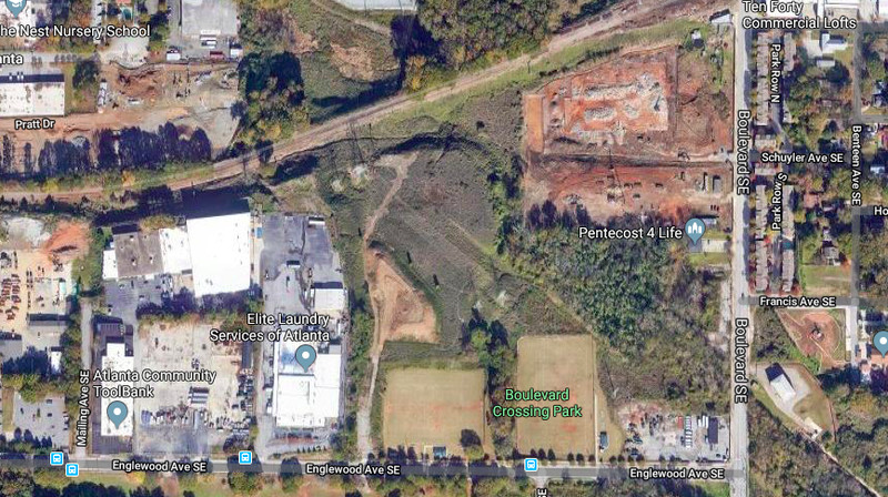 An aerial view of a planned park with several buildings and the Beltline corridor around it.