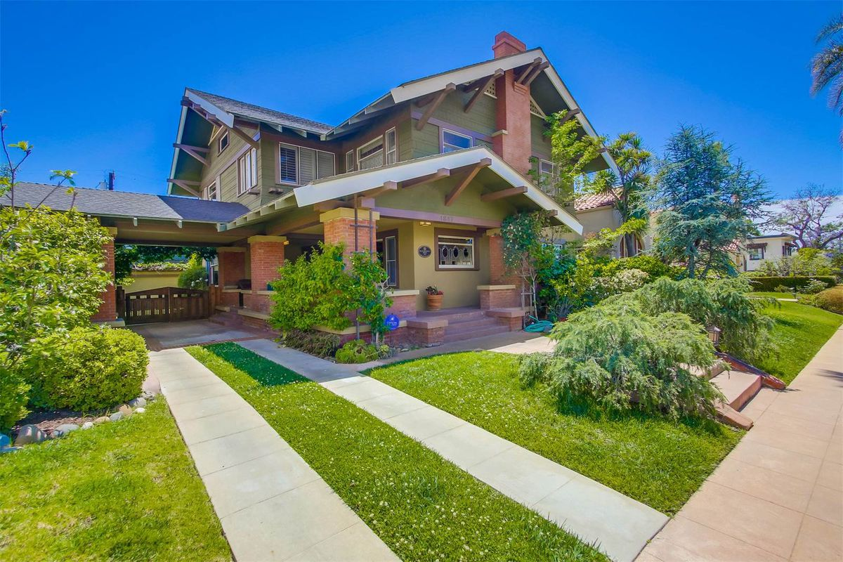 Exterior shot of Craftsman home with Tudor touches set behind a lawn and driveway.