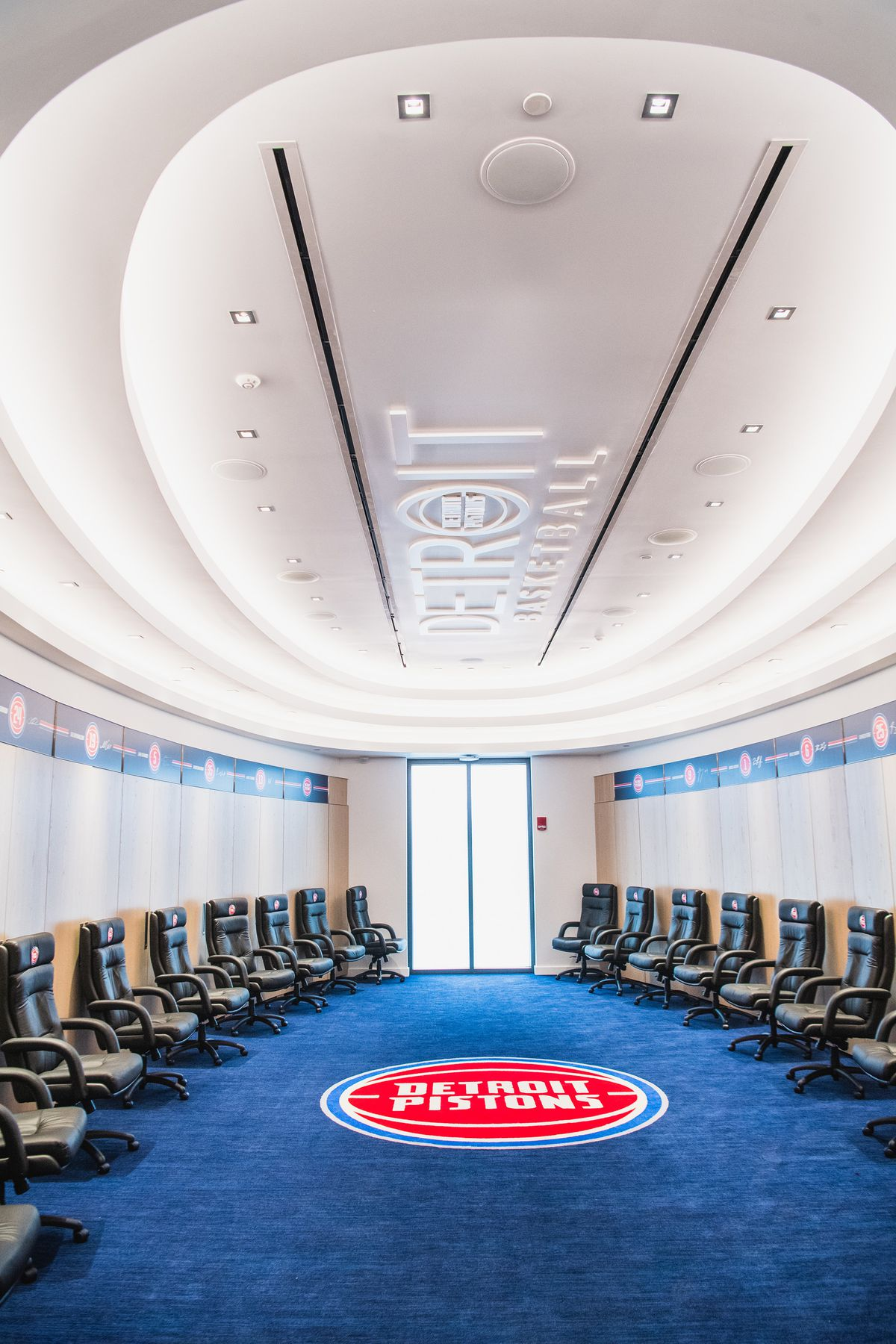 Two rows of black chairs sit opposite each other. On the carpeted floor is the Detroit Pistons logo.