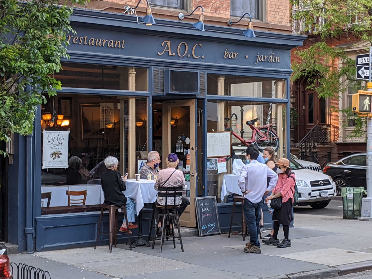 Small groups of diners sitting outside French restaurant A.O.C. in the West Village