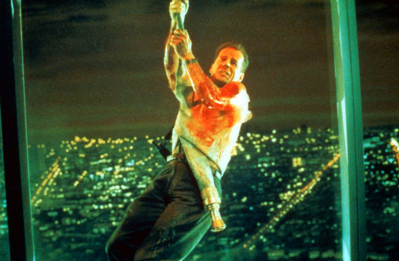A movie still from Die Hard. Bruce Willis, covered in blood and sweat, propels down a building. City lights sprawl out in the background.