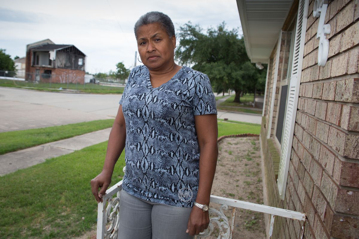A woman wearing a blue patterned shirt stares into the camera while standing on her porch near a strip of grass and a sidewalk with a dilapidated home in the background.