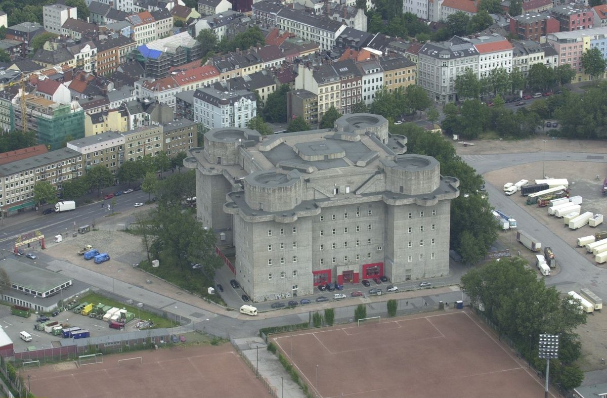 An aerial view of an imposing square-like, tall concrete bunker surrounded by trees and city streets.