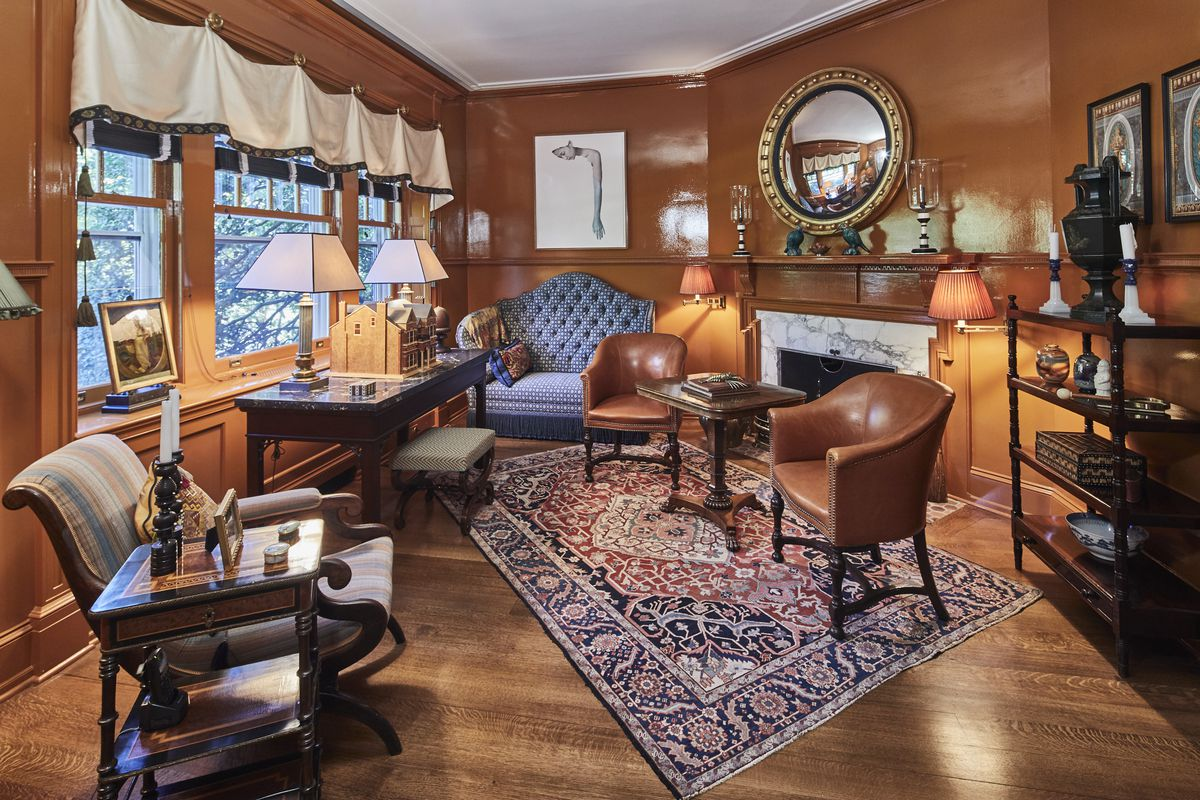 A brown sitting room has an Oriental rug, leather chairs, and wooden floors.