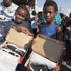 Pershais Comer, 9, and Cameron Comer, 8, posing with their new shoes.   Rick Majewski/For the Sun-Times