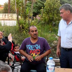 Mayor Iosif-Nampil Morant, right, listens to camp residents at the Kyllini refugee camp in Myrsini, Greece, July 11, 2016. Morant, a native Syrian and the first foreign-born mayor elected in Greece, had the idea to turn the LM Village resort into a refugee camp for families.