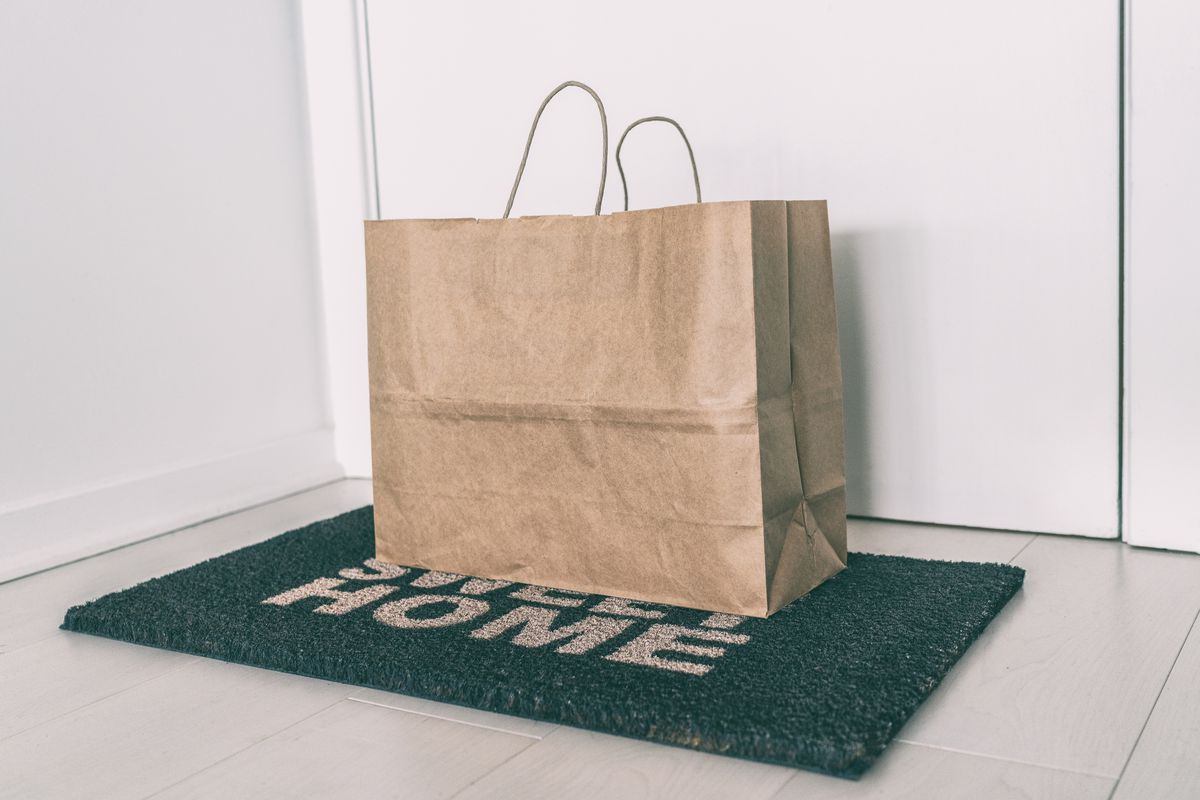 A bag of food delivery left on top of a welcome mat near a white door