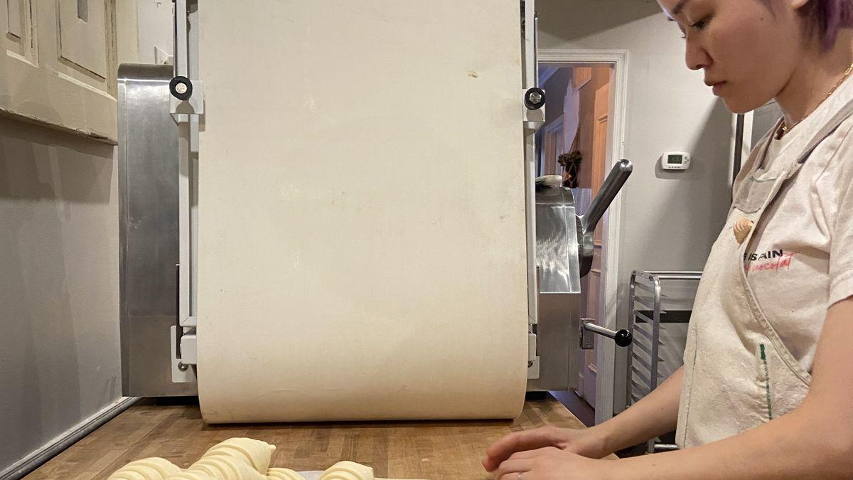 Head baker Yuri Oberbillig rolls dough next to a tray of raw croissants.