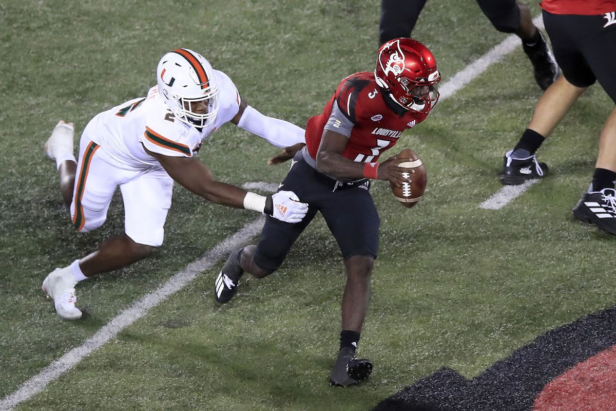 Malik Cunningham of the Louisville Cardinals runs with the ball while defended by Quincy Roche of the Miami Hurricanes at Cardinal Stadium on September 19, 2020 in Louisville, Kentucky.