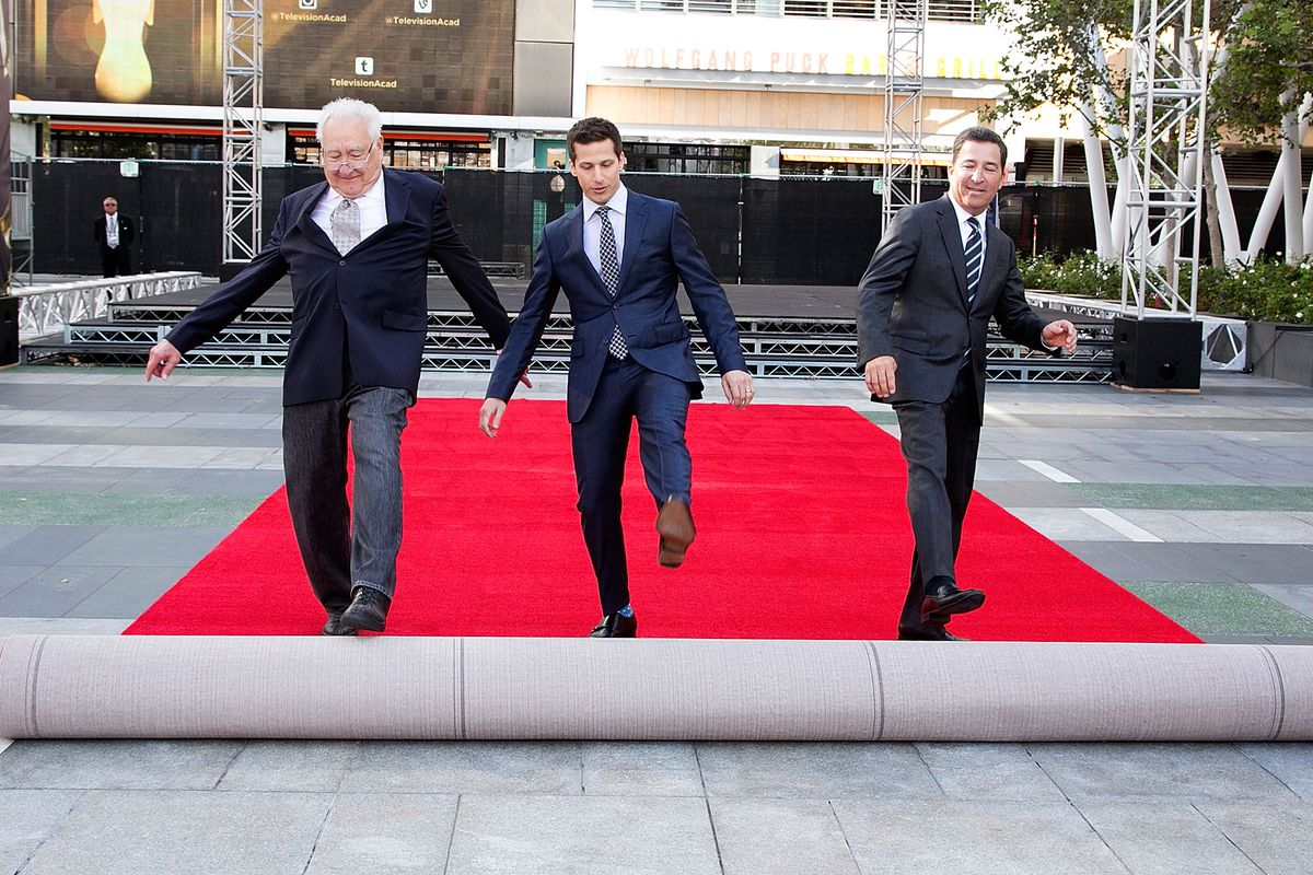 Andy Samberg, host, rolls out the red carpet while flanked by Emmys execs.