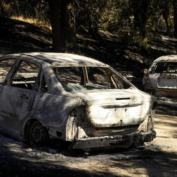 Burned out cars sit near a home that was destroyed by a wildfire in Santa Margarita, Calif., Wednesday, June 28, 2017.