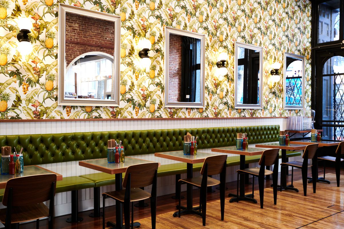 Bae's Chicken has a green banquette with two-tops, wooden chairs, and cups of silverware on each table