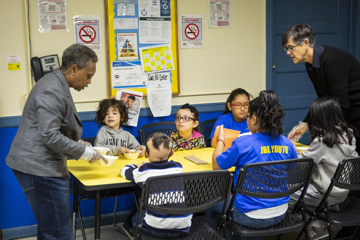 Mayor Lori Lightfoot and her wife Amy Eshleman pass out breakfast to Chicago Public Schools students at a teachers' strike contingency site, the Gads Hill Center, on Friday, Oct. 18.