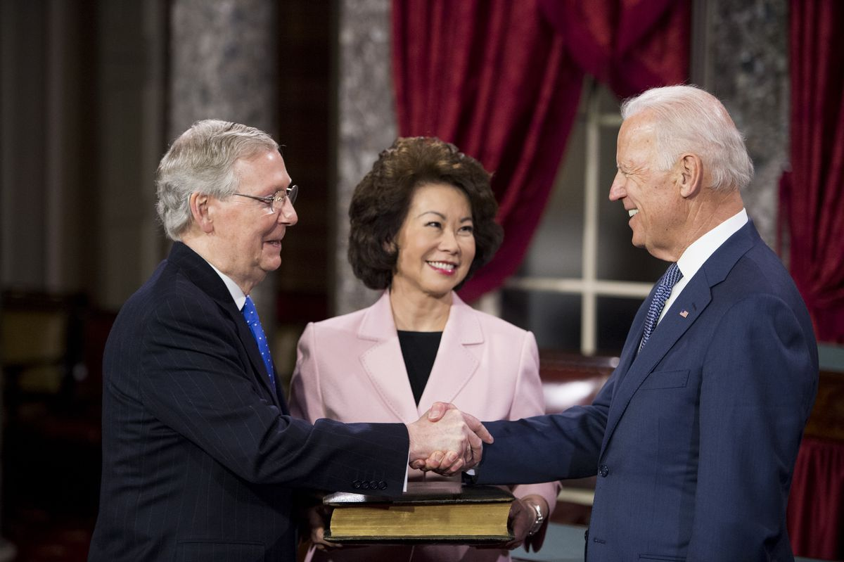 Senate majority leader Mitch McConnell shaking hands with Vice president Joe Biden while McConnell's wife Elaine Chao smiles between them.