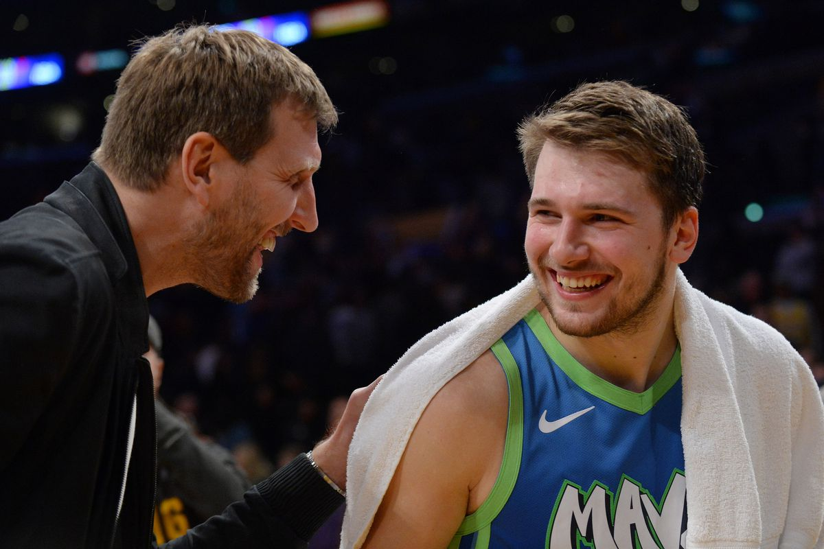Dallas Mavericks forward Luka Doncic meets with former player Dirk Nowitzki following the 114-100 victory at Staples Center.