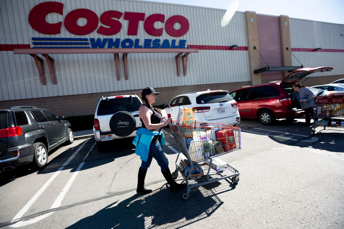 """Lisa Russo pushes her shopping cart to her car in the Costcoparking lot in Murray on Thursday, March 12, 2020. Russo waited in line for 40 minutes while many shoppers like herself stocked up on items as a precaution against the spread of the coronavirus. """"I don't want to give into the fear, but I have four kids at home, and it's important that I just be prepared,"""" Russo said."""