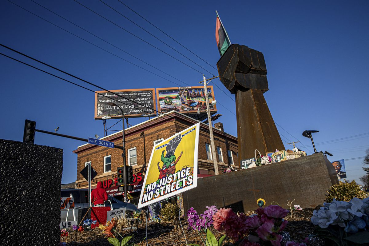Beneath a cobalt sky, the sign for Cup Foods, where Floyd attempted to make the purchase that led to his death is visible. In the foreground is a memorial — a mass of colorful flowers strewn about a massive metal fist raised skyward, and topped by a pan-African flag.