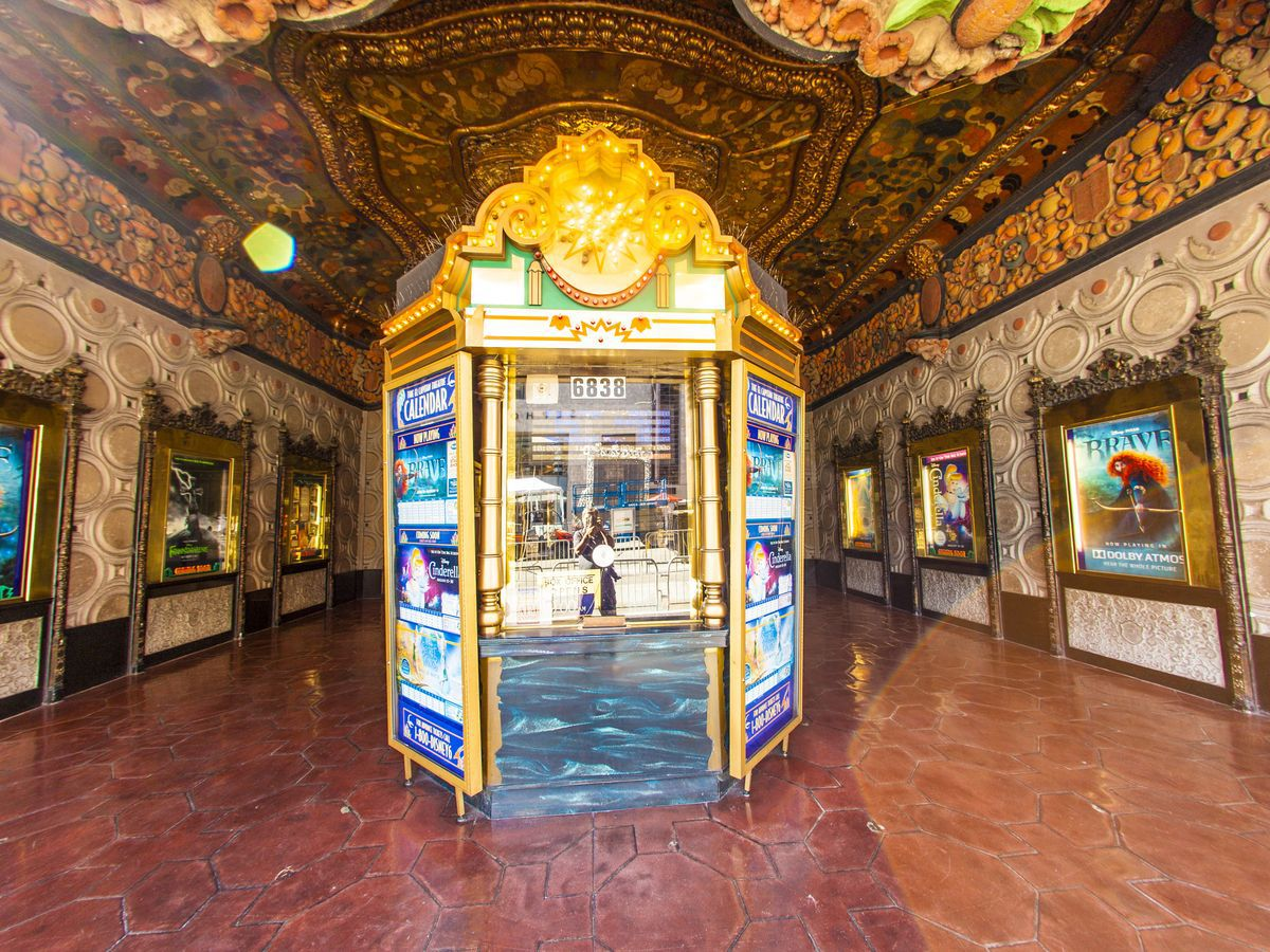 The inside of a theater. There is a box office structure in the center. The walls are ornately decorated with mosaics and tile-work. There are movie posters hanging in lit frames on the walls.