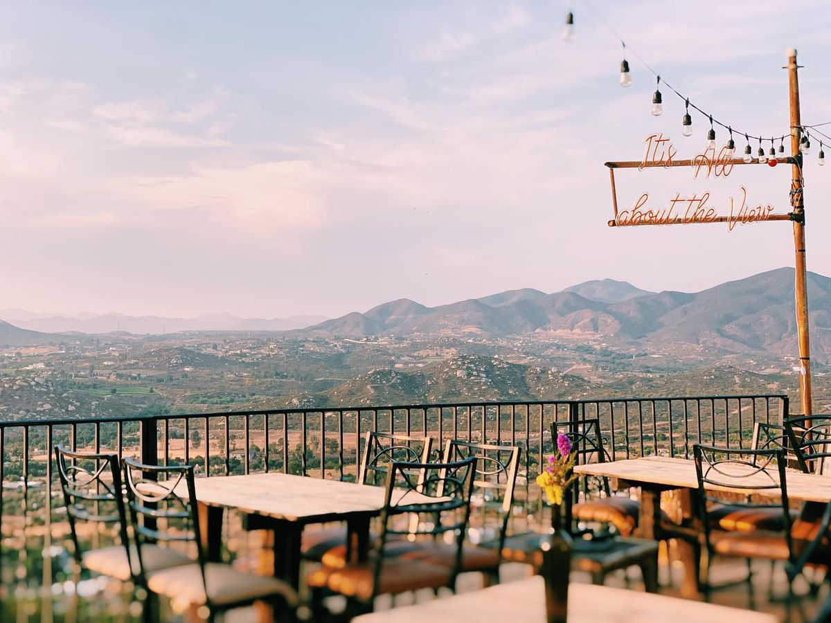 """An outdoor patio overlooking a valley below and mountains in the distance. There are empty tables, set with simple wood chairs, beneath string lights and a sign that reads """"It's all about the view"""""""