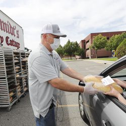 Steve Borg, owner of Schmidt's Pastry Cottage, hands out two loaves of bread to an area resident at Cyprus High School in Magna a Free Bread Project giveaway on Sunday, May 17, 2020.