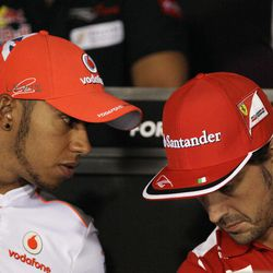 Ferrari driver Fernando Alonso, right, of Spain, talks with McLaren Mercedes driver Lewis Hamilton, of Britain, during a press conference at the Monza Formula One circuit, in Monza, Italy, Thursday, Sept. 6, 2012. The Formula One race will be held on Sunday.