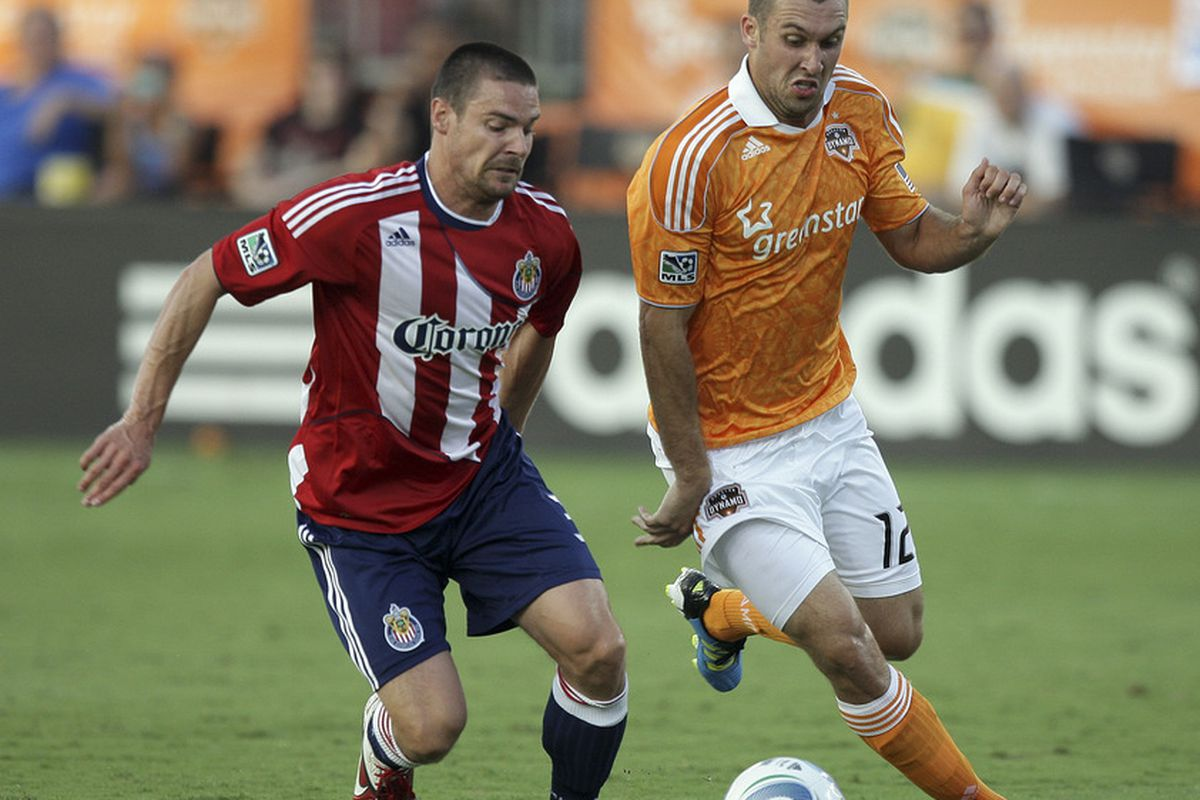 HOUSTON - JUNE 11:  Will Bruin #12 of the Houston Dynamo attempts to get around Heath Pearce #3 of Chivas USA at Robertson Stadium on June 11, 2011 in Houston, Texas.  (Photo by Bob Levey/Getty Images)